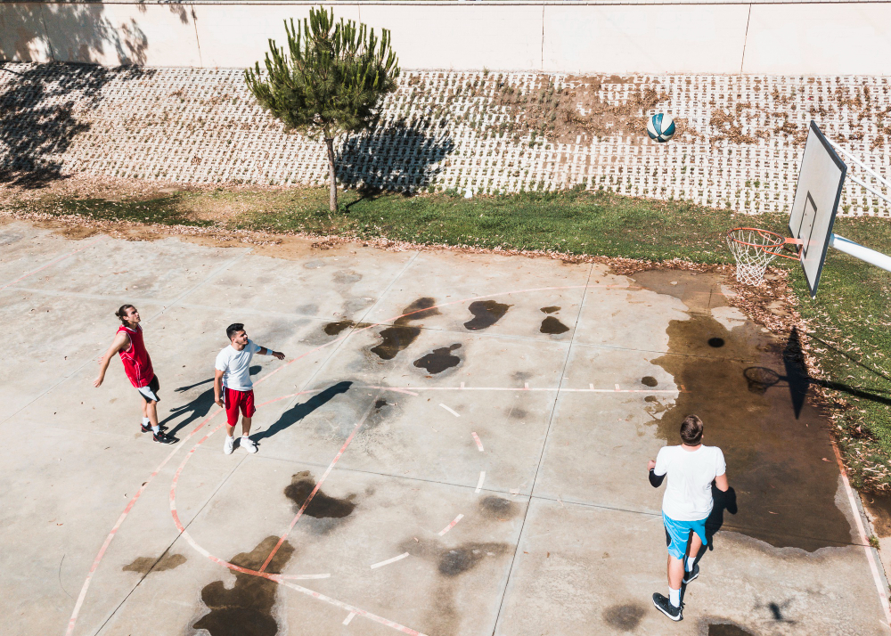 three-players-playing-basketball-outdoors-court